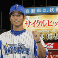 The BayStars' Masayuki Kuwahara poses for photos after hitting for the cycle on July 20, 2018. His achievement is shown on the scoreboard message behind him.