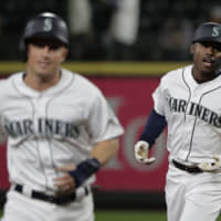 Seattle's Kyle Lewis (right) rounds the bases with teammate Kyle Seager after hitting a three-run homer against Cincinnati in the seventh inning on Wednesday night.