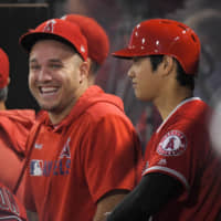 Angels outfielder Mike Trout (left) laughs next to teammate Shohei Ohtani during the first inning of a game against the Indians on Sept. 10 in Anaheim, California.