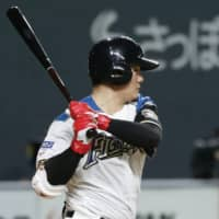 Fighters first baseman Kotaro Kiyomiya hits a bases-loaded single in the eighth inning against the Hawks on Sunday at Sapporo Dome.