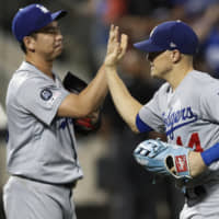 Dodgers reliever Kenta Maeda (left) celebrates his team's victory over the Mets with right fielder Enrique Hernandez on Sunday in New york.