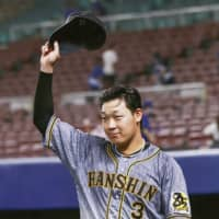Tigers infielder Yusuke Oyama tips his cap to the crown after his teams win over the Dragons on Friday in Nagoya. | KYODO