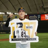 Giants manager Tatsunori Hara poses for photo after setting a club record with his 1,067th win on Friday at Tokyo Dome. | KYODO