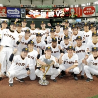 Giants captain Hayato Sakamoto holds the trophy as Yomiuri players pose for photos on the mound after winning the Central League title on Friday. | KYODO
