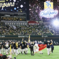 The Hawks carry the Pacific League pennant around PayPay Dome on Tuesday in Fukuoka. | KYODO