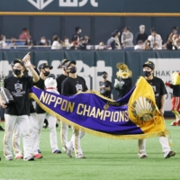 The Hawks carry the championship banner after winning the Japan Series on Wednesday.   KYODO