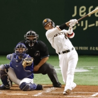 Giants shortstop Hayato Sakamoto hits a two-run double against the Dragons during the third inning at Tokyo Dome on Wednesday. | KYODO