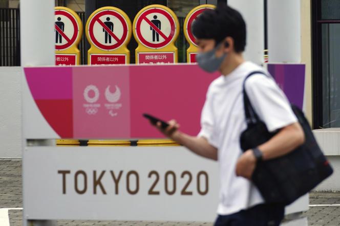 Un homme portant un masque passe devant une affiche des Jeux olympiques de Tokyo, le 11 mai 2021.