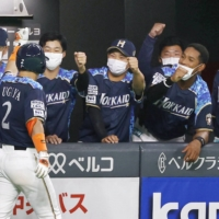 Fighters players congratulate Kenshi Sugiya following his solo home run in the third inning at Sapporo Dome on Friday.   KYODO