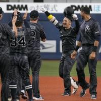 Takahiro Okada lifts his arms in celebration after hitting a sayonara single against the Carp in Osaka on Sunday. | KYODO