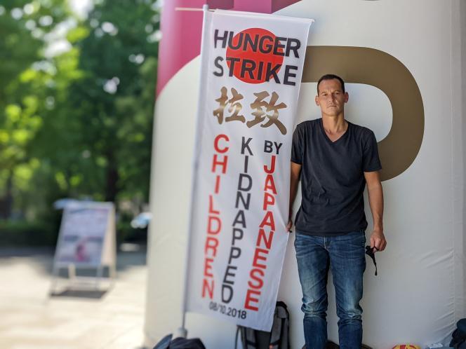 Vincent Fichot, père de deux enfants, proteste contre les«enlèvements» d'enfantspar un parent, près du stade olympique de Tokyo, au Japon, le 21 juillet 2021.