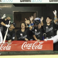 Lotte's Takashi Ogino is congratulated by his teammates after hitting a game-tying home run against Orix during the ninth inning in Kobe on Thursday. | KYODO